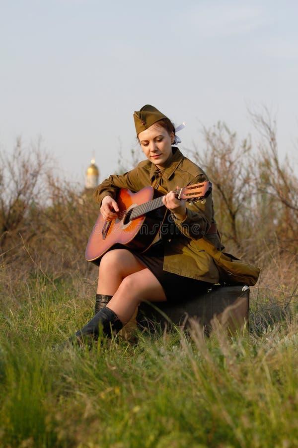 二战制服的苏联女兵弹吉他 免版税库存照片