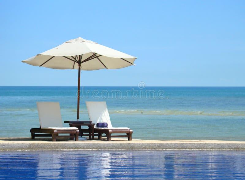 二把椅子和在海滩的空白伞 免版税库存图片