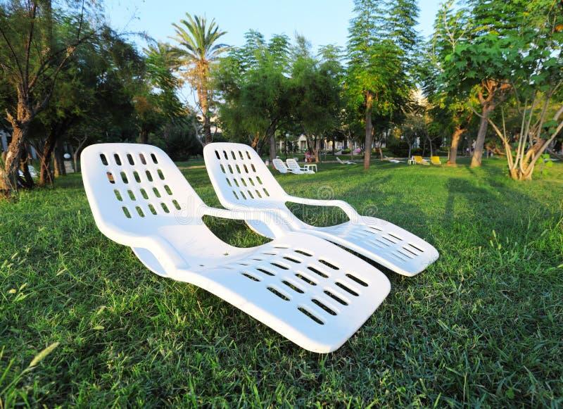 二把空的塑料椅子在公园。 重新创建 库存照片