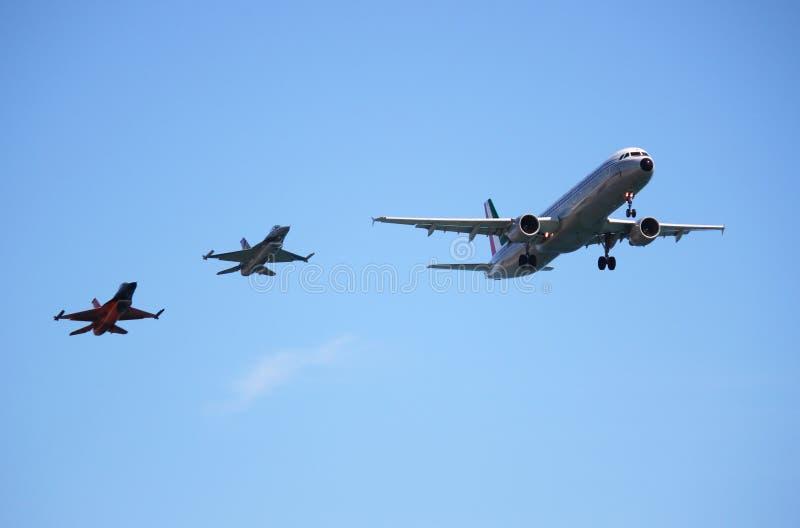二架战斗机伴随于的空中巴士A320航空器 免版税库存图片