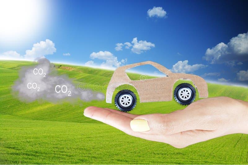 二氧化碳与纸板模型汽车的污染概念有尾气烟云的在妇女手,自然本底上与绿草和 免版税库存照片