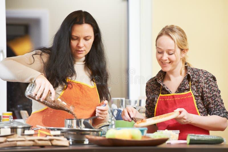 二烹调在厨房里的妇女 图库摄影