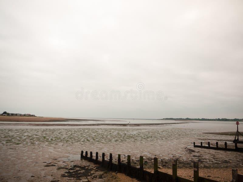 阴云密布夏天场面海滩groynes小卵石mudflats 库存图片