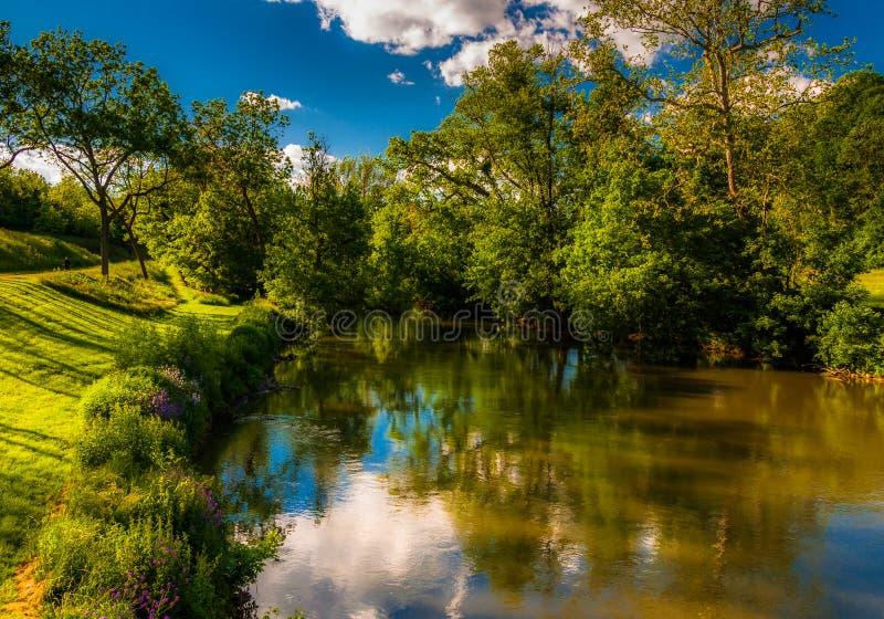 云彩和树的反射在安提俄珀Creek, Antietam的N 库存图片