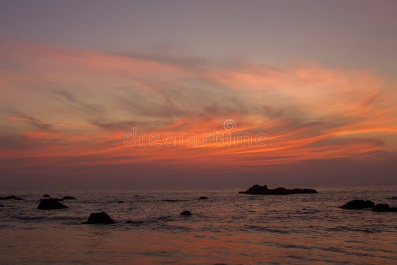 云彩明亮的红线在日落深蓝天空的反对平衡的海和岩石 库存图片