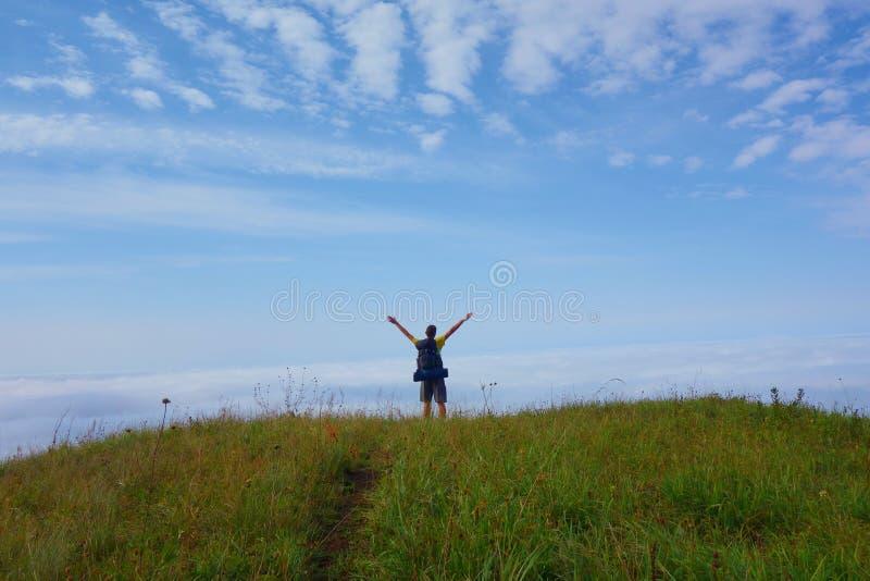 云彩海在有一个年轻人的Lagodekhi国家公园带领一条的供徒步旅行的小道的染黑Rock湖,高加索山脉, Georgi 库存照片