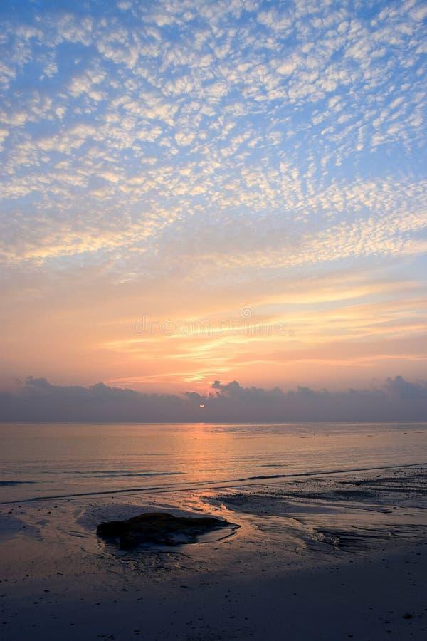 云彩的样式在早晨明亮的天空的与在天际的朝阳在海洋 库存图片