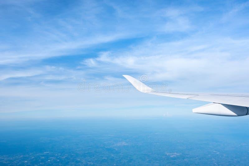 云彩鸟瞰图和天空和土地有飞机翼的从飞机窗口,旅行和运输概念 免版税图库摄影