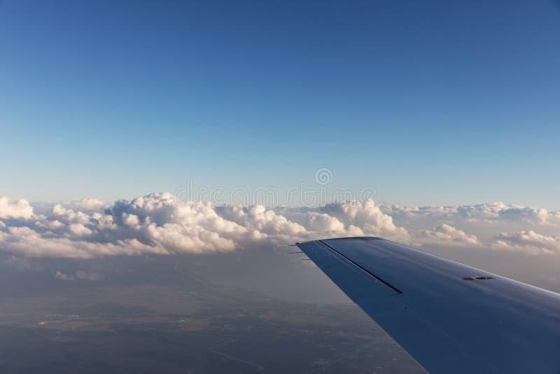 云彩鸟瞰图由在佛罗里达,从航空器的看法的晚上太阳点燃了在飞行期间 免版税库存照片