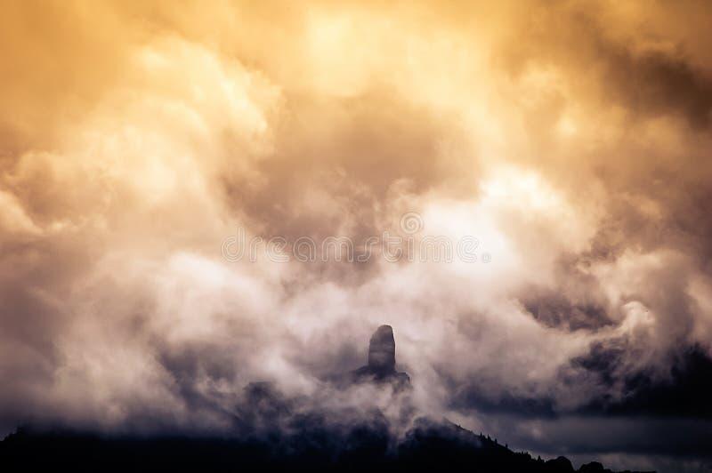 云彩围拢的大岩石在日落 库存照片