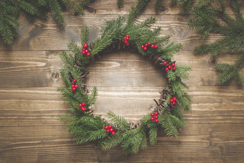 云杉的分支圣诞节花圈用在木板的霍莉莓果 平的位置 顶视图 图库摄影