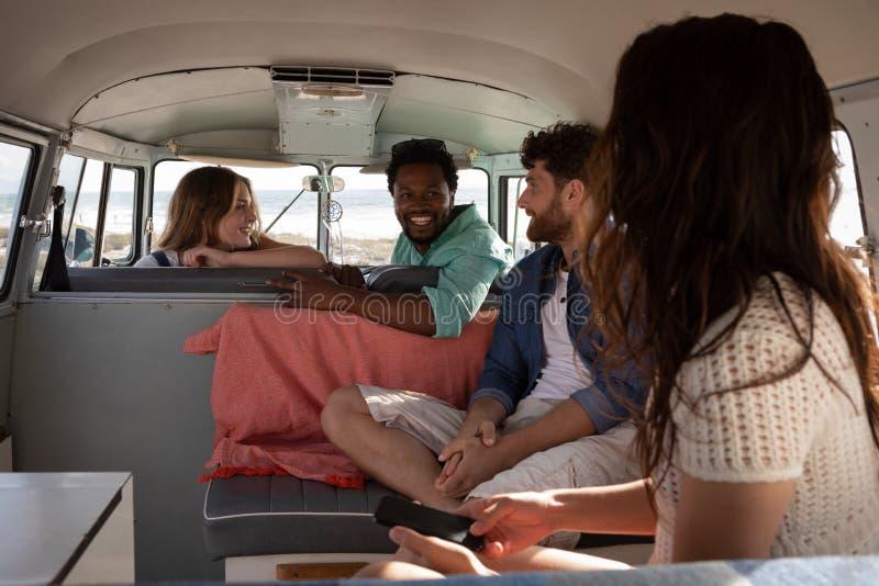 互动与其中每一的小组朋友其他在露营者货车在海滩 库存图片