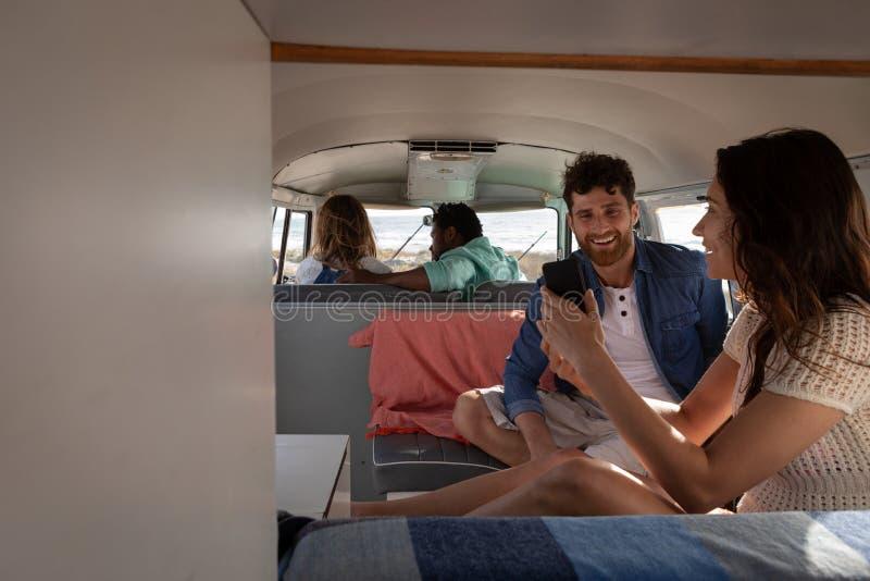 互动与其中每一的小组朋友其他在露营者货车在海滩 免版税库存图片