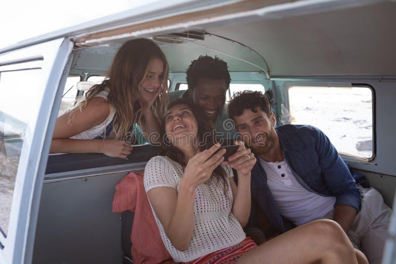 互动与其中每一的小组朋友其他在露营者货车在海滩 免版税库存照片