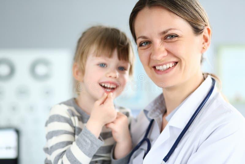 互动与女性医生的微笑的逗人喜爱的矮小的患者 免版税图库摄影