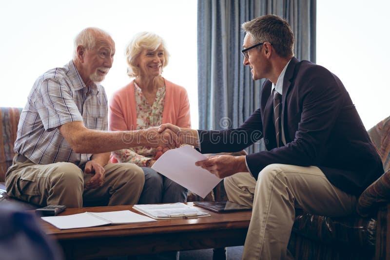 互动与资深夫妇的男性医师在养老院 免版税图库摄影