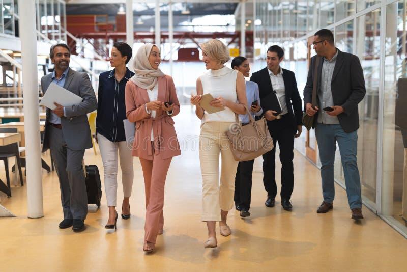 互动互相的商人,当走在一个现代办公室时 免版税图库摄影