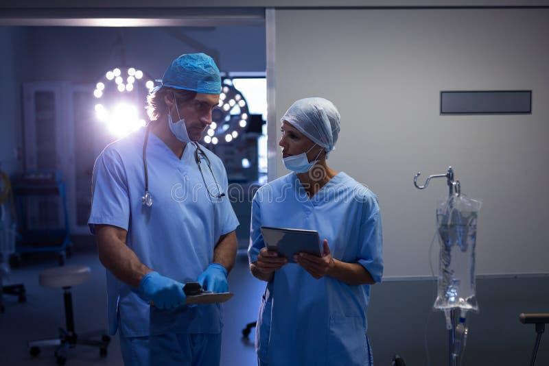 互动互相的外科医生,当拿着数字片剂在医院时 免版税库存图片