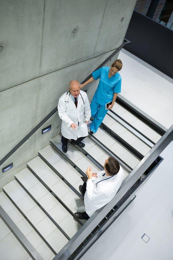 互动互相的大角度观点的医生和外科医生在楼梯 免版税库存图片