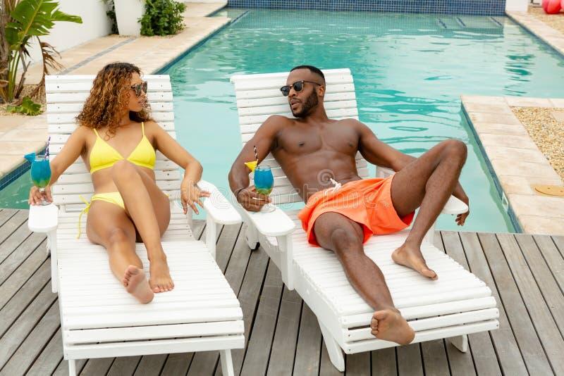 互动互相的夫妇,当放松在太阳懒人时 免版税库存图片