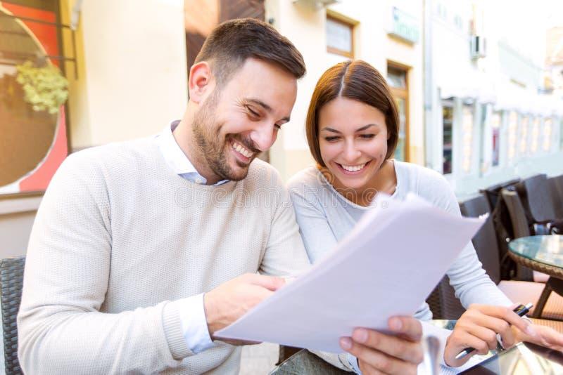 互动年轻的夫妇,当食用咖啡时 免版税图库摄影