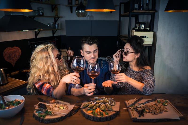 互相三个朋友谈话故事在酒吧柜台的现代家庭厨房里 免版税库存照片