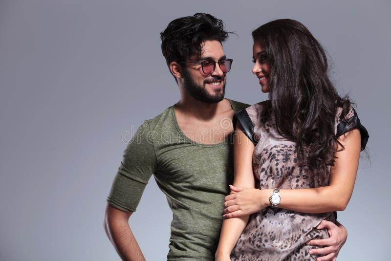 互相微笑年轻偶然的夫妇 免版税库存照片
