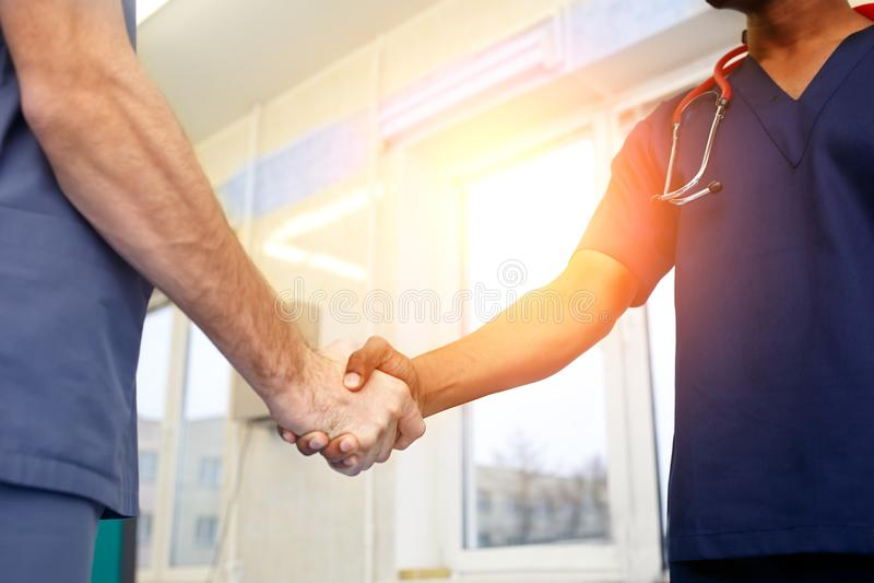 互相握手的两位年轻医生 年轻医生多种族队  免版税库存图片