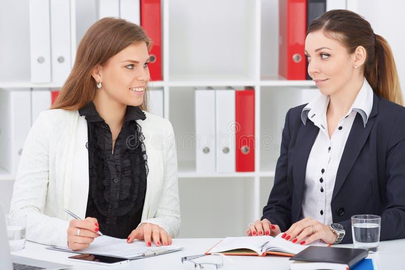 互相看在关于草稿的讨论过程中的对年轻微笑的同事 免版税库存图片