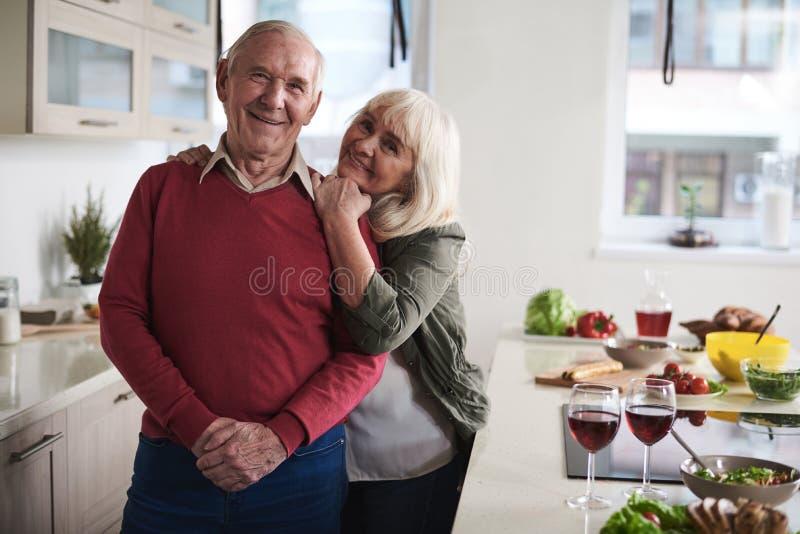 互相结合在晚餐的微笑的资深夫妇 免版税库存照片