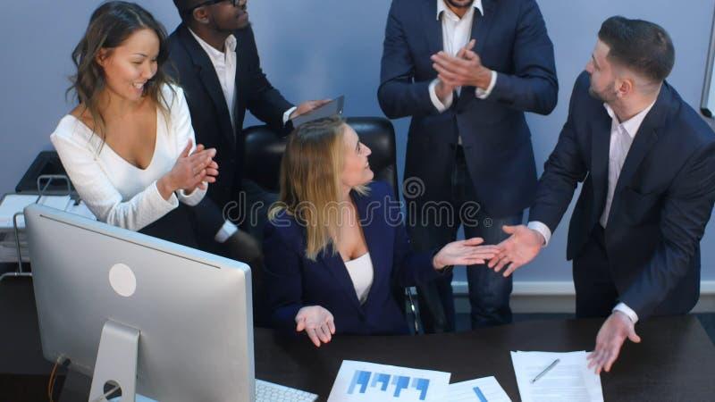 互相鼓掌在办公室的企业多种族队 免版税库存照片