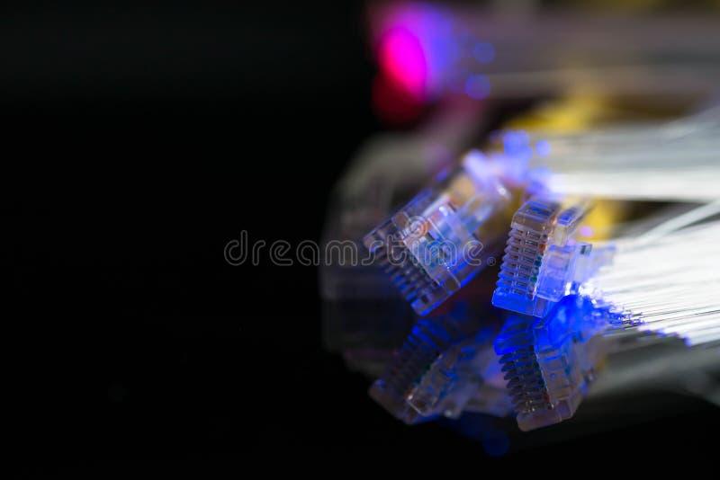 互联网缚住,射击的光纤关闭黑发光的表面上 库存照片