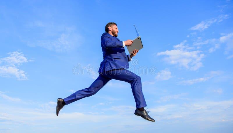 互联网连接在网上那么快速地提高速度 商人膝上型计算机满意的质量 有膝上型计算机跃迁或飞行的人 图库摄影
