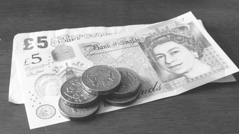 五一1英镑硬币新的5磅笔记和老五元美钞BW 免版税库存图片
