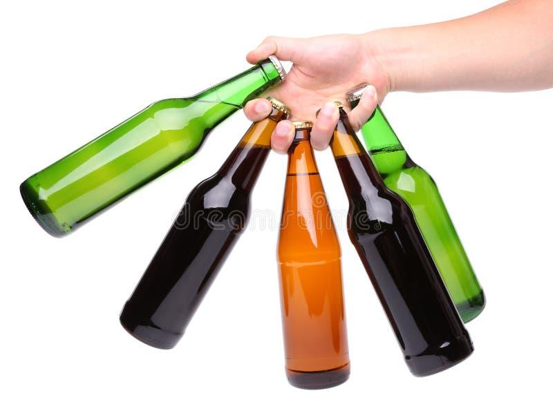 五个啤酒瓶和手 免版税库存图片