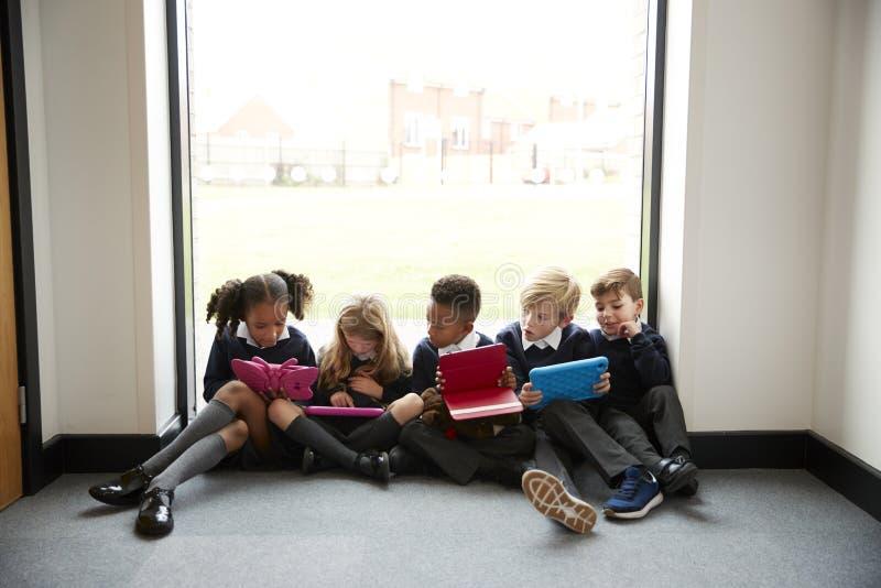 五个小学孩子连续坐在一个窗口前面的地板在看片剂计算机,fron的学校走廊 免版税库存照片