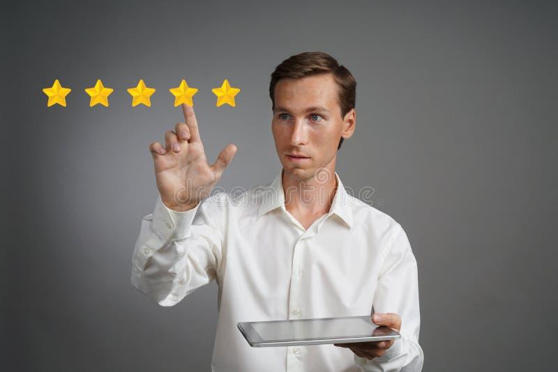 五个星规定值或等级,基准点概念 有片剂个人计算机的人估计服务,旅馆,餐馆 免版税库存照片