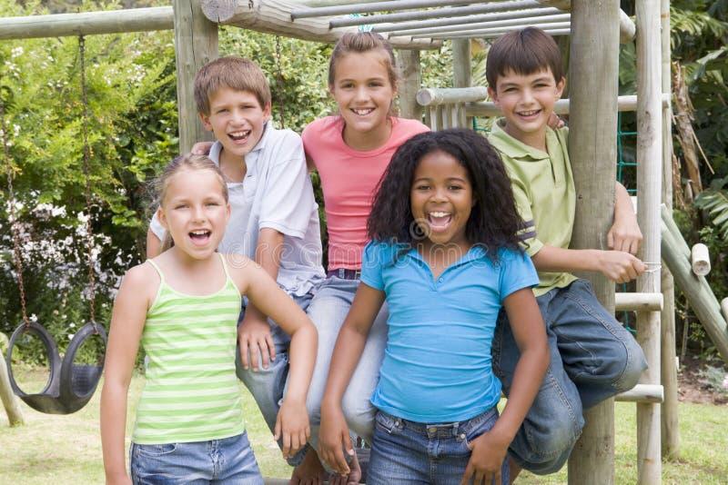 五个朋友操场微笑的年轻人 库存照片