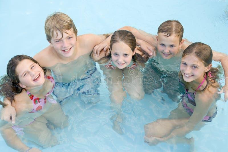 五个朋友池微笑的游泳年轻人 免版税库存照片