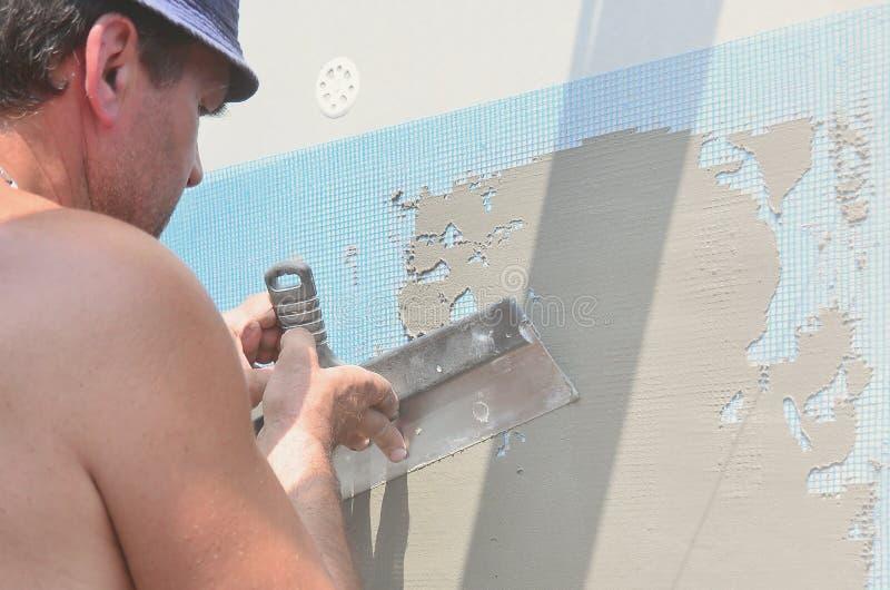五十岁有墙壁的体力工人涂灰泥工具的更新房子 更新墙壁和角落与小铲的石膏工和 库存图片