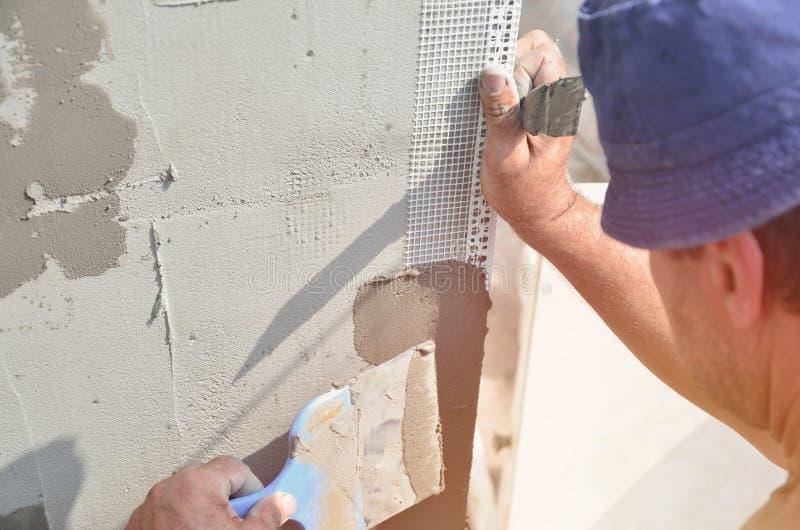 五十岁有墙壁的体力工人涂灰泥工具的更新房子 更新墙壁和角落与小铲的石膏工和 免版税库存图片
