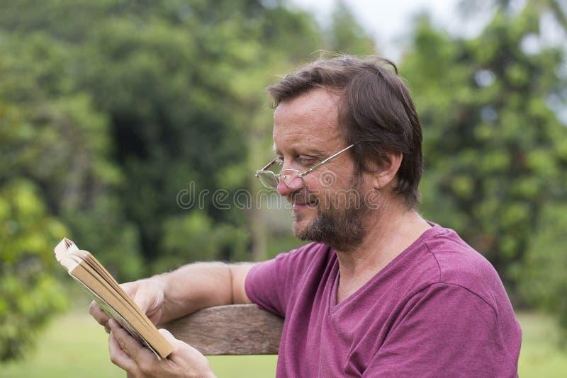 五十岁画象读书的白种人人室外在公园在一个晴朗的夏日期间 免版税图库摄影