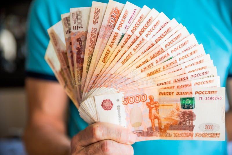 五千俄罗斯卢布的衡量单位 在男性手上隔绝的捆绑钞票 5000卢布 五千现金 免版税库存照片