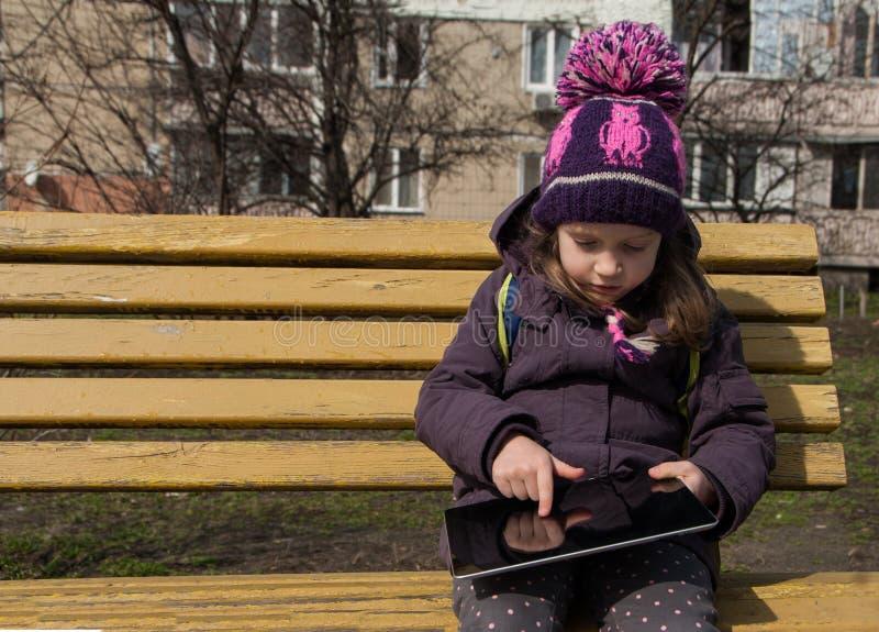 五岁在长凳的女孩sittion和接触与手指她的数字片剂,户外 免版税库存图片