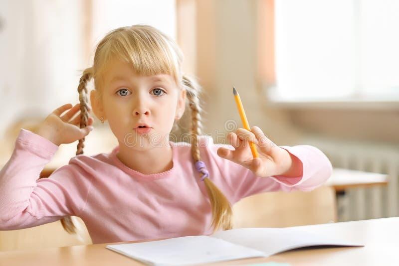 五岁坐在教室和写的白肤金发的女孩 免版税图库摄影