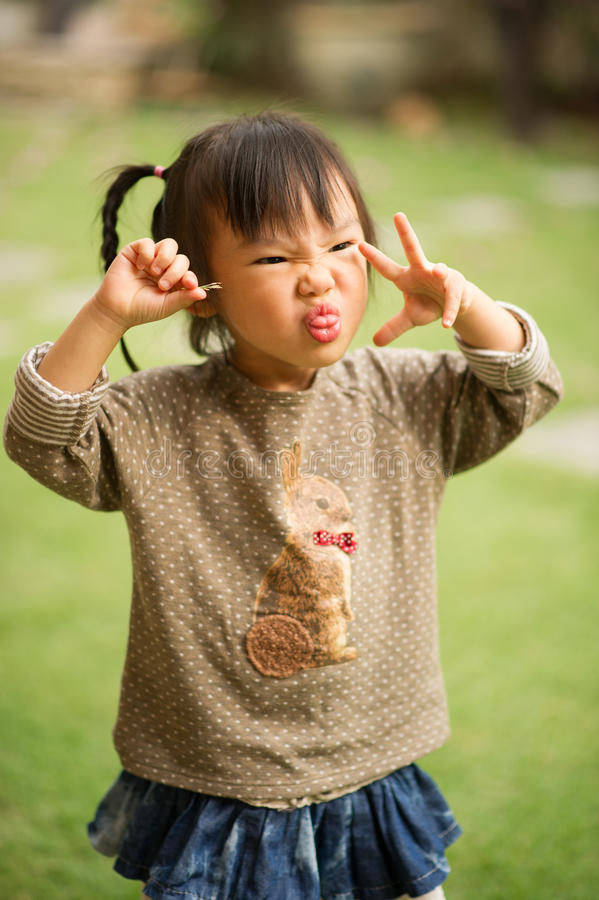 五岁的中国亚裔女孩在做面孔的庭院里 库存图片