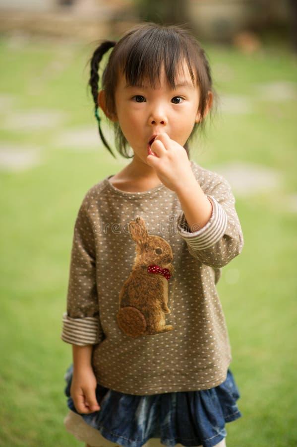 五岁的中国亚裔女孩在做面孔的庭院里 免版税库存图片