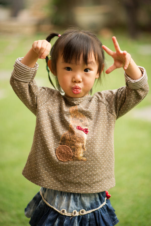 五岁的中国亚裔女孩在做面孔的庭院里 库存照片