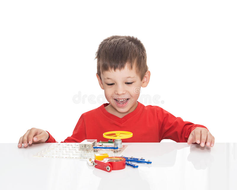 五岁的男孩坐在一张白色桌上并且扮演一位电子设计师 库存照片