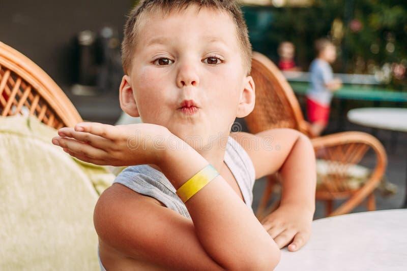 五岁的白种人男孩做鬼脸在夏天咖啡馆的一张桌上 孩子和夏天休假 旅馆镯子在手边 免版税库存图片
